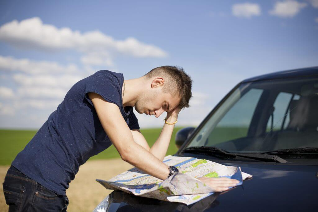 Young man confused looking at a road map outside of his car